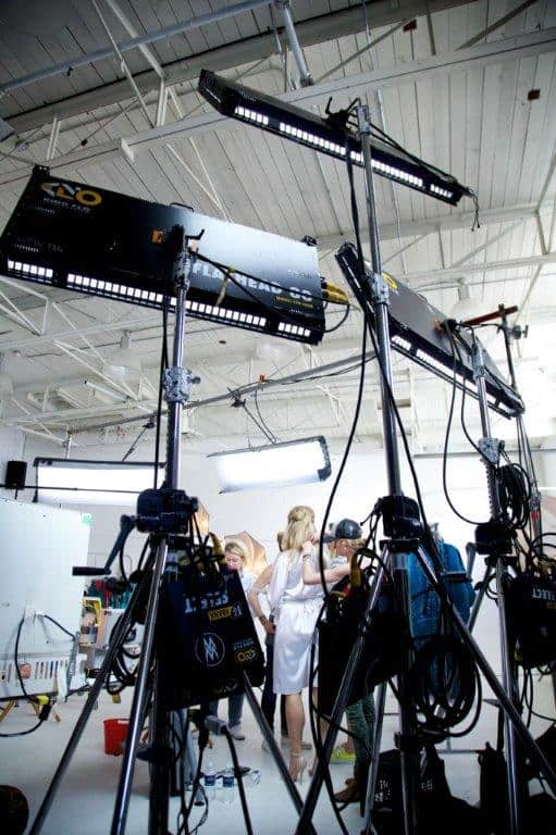 Lighting panels up high in a circular fashion at a film shoot with a white screen in the background