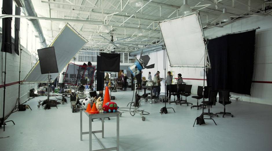 Film shoot taking place with lighting and film equipment filling the space