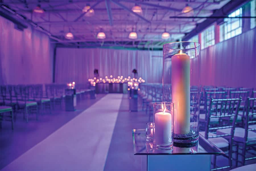 Two large candles in the forefront as Airship37 is lit by candlelight with a large carpet runner down the large venue space