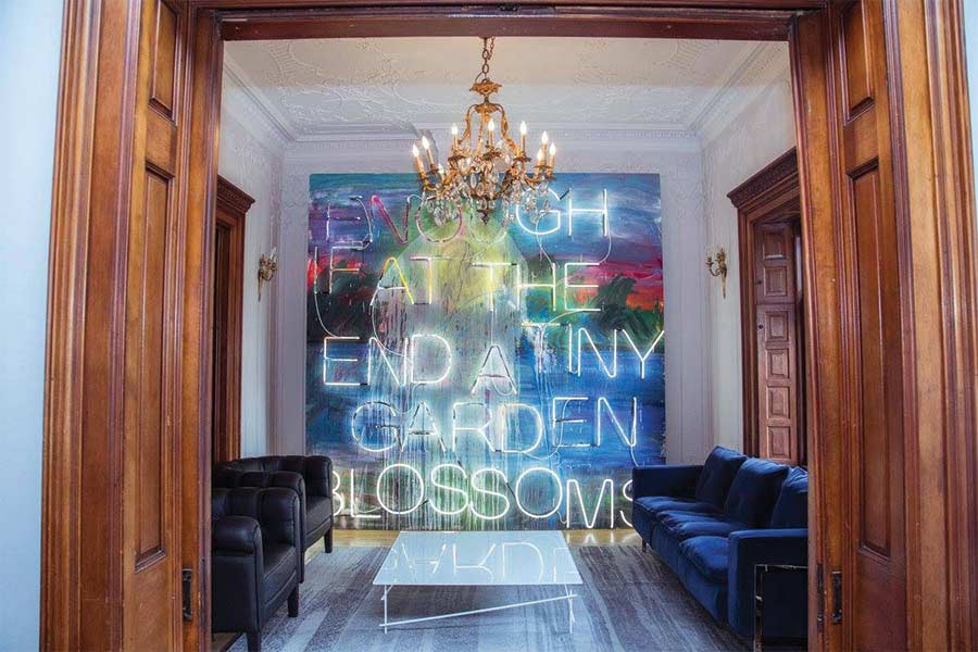 """Artwork by Thrush Holmes that says in zeon lights """"enough if at the end a tiny garden blossoms"""""""