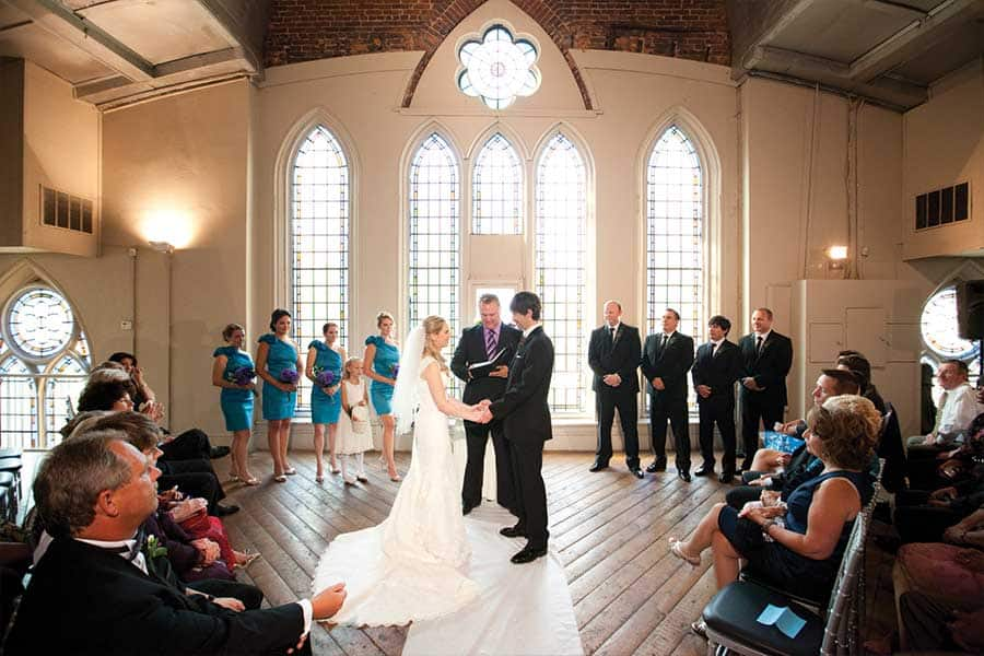 Wedding ceremony at Berkeley Church with stained glass windows and the wedding party behind the bride and groom