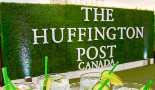 Outside on the Patio of the Airship37 Event Venue there is a Large grass wall with The Huffington Post in white letters with cocktail drinks in front
