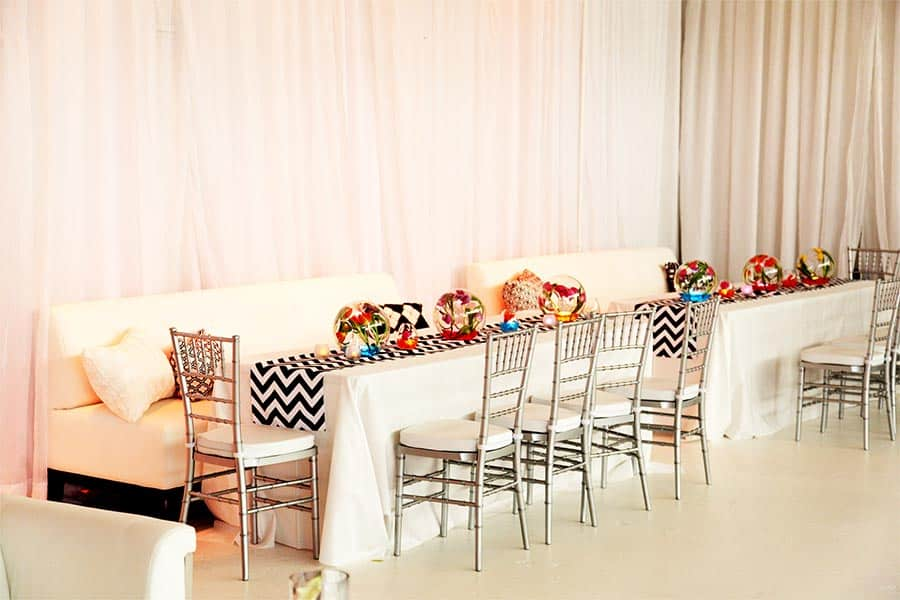 A couple of couches sit at Airhsip37 with colourful pillows to match vibrant Bar Mitzvah themed party