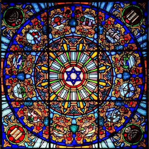 Stained glass piece with very detailed design. Colours are yellow, red, blue, orange