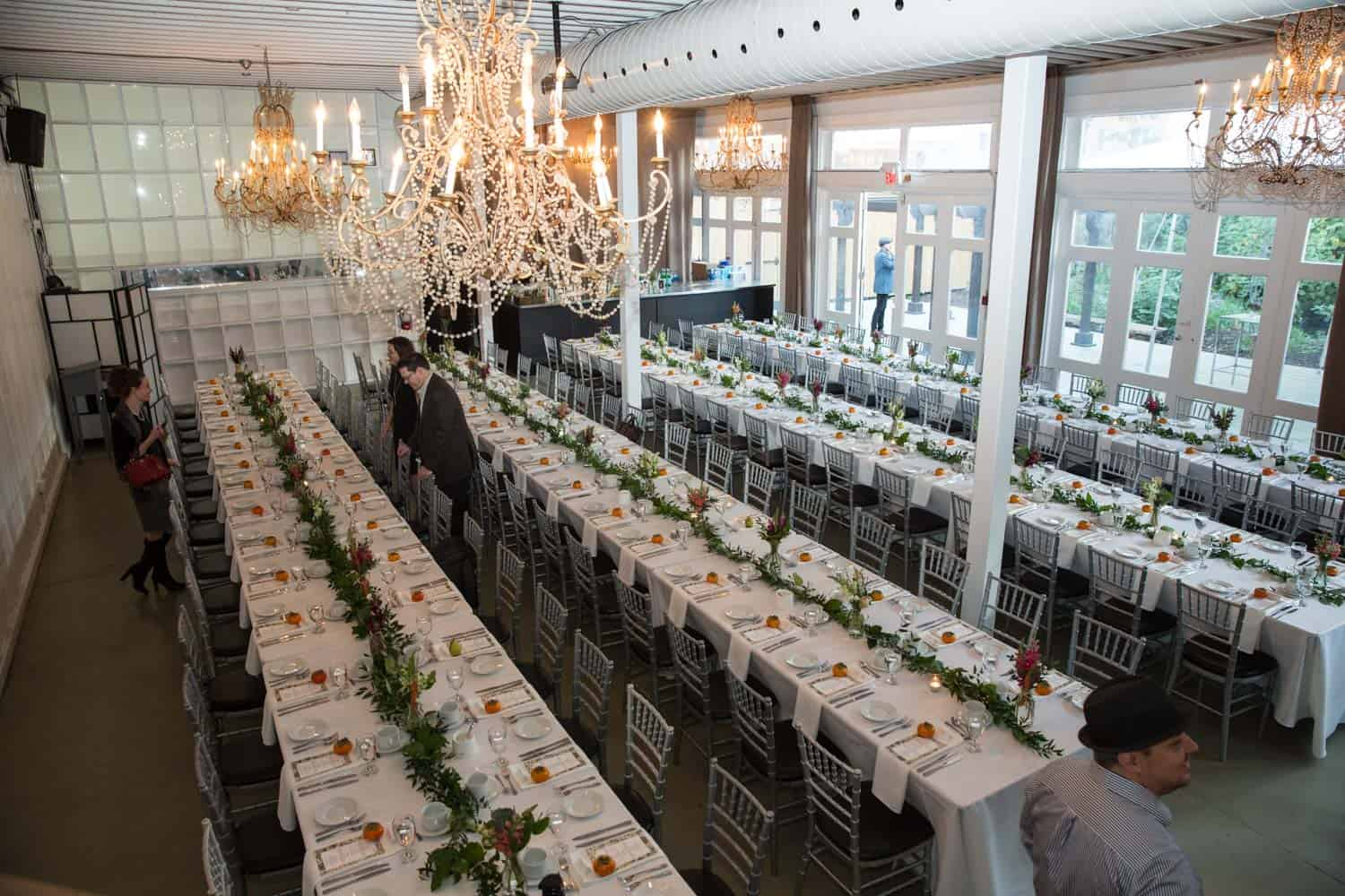 long tables set with multiple chairs and chandeliers hanging above