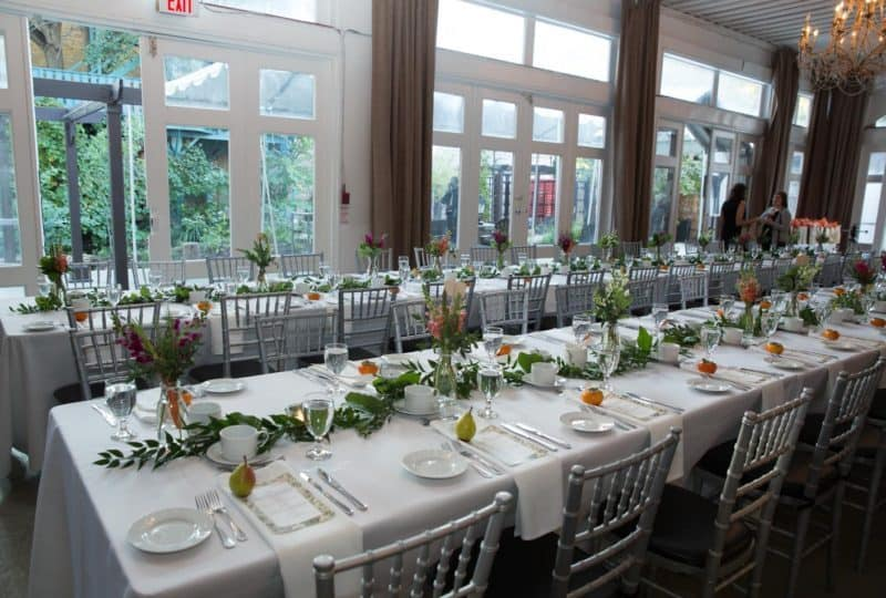 Two rows of tables at the Berkeley Field House with green leafy centrepiece runners