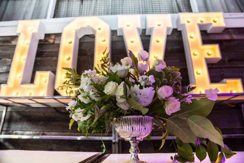 """White flower arrangement sits is a silver vase with a big sign that says """"LOVE"""" in the background"""