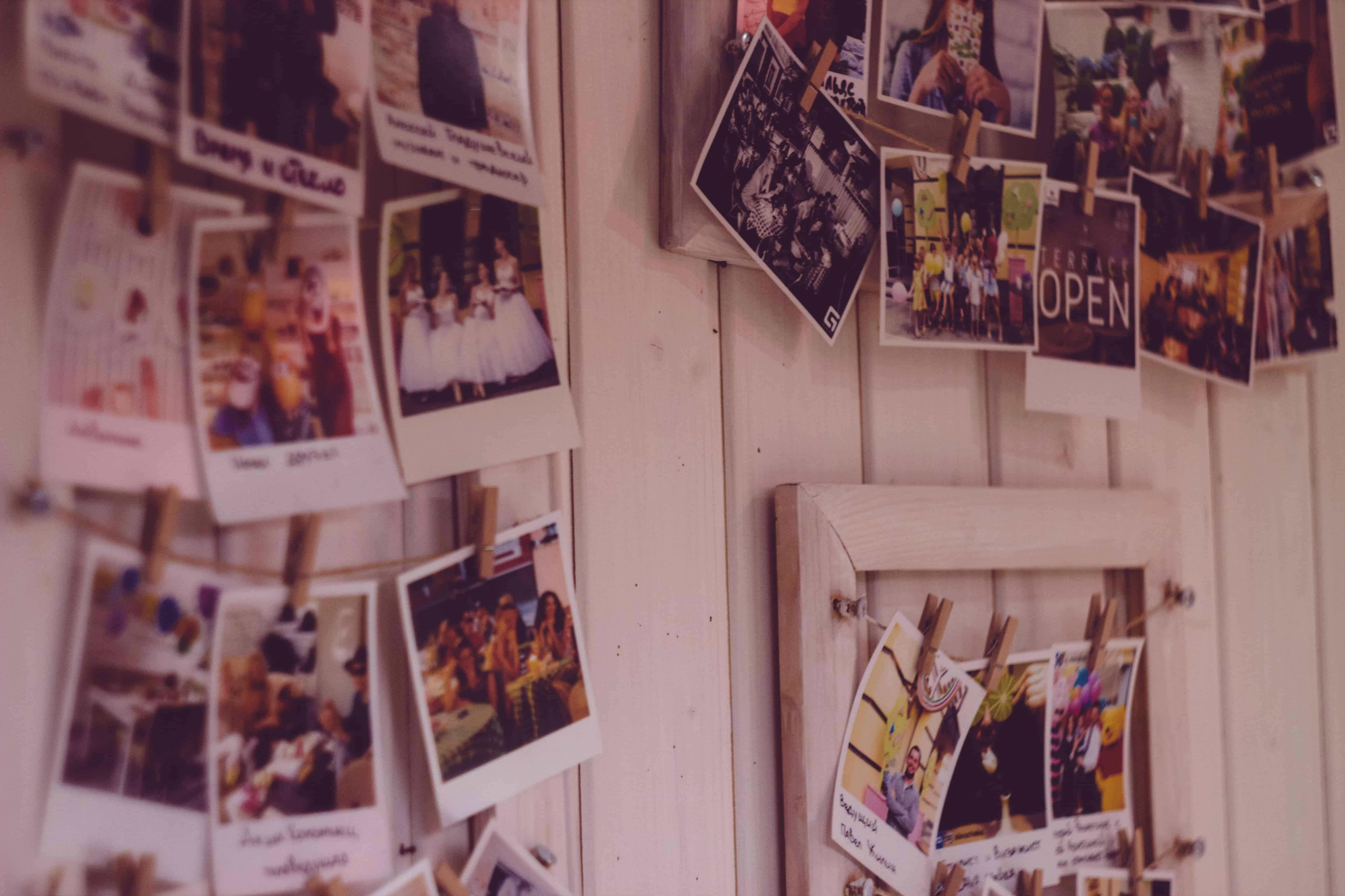 Polaroid photos hang in a collage with wooden clips and string