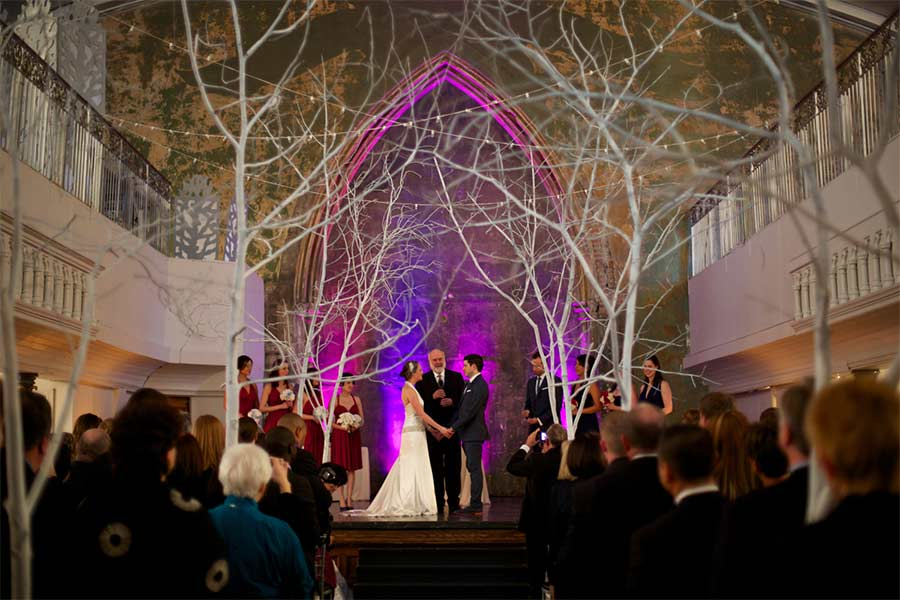 Bride and groom getting married in the Berkeley Church under trees and string lights in the winter.