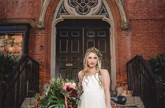 Bride stands at the front entrance of the Berkeley Church with her bicycle staring straight at the photographer