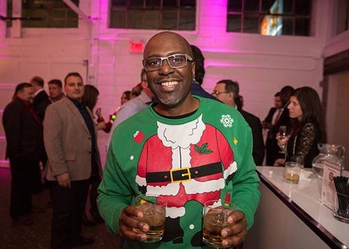 Guest at Christmas party smiles while holding a drink