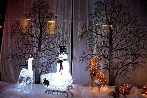 Artificial snowman and reindeer decorations on display at the airship37 venue with trees in the background