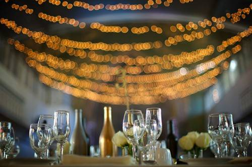multiple string lights hang lit up and table is set with wine glasses in the forefront