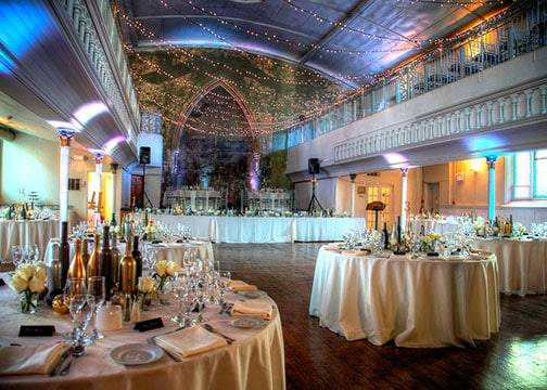 Circular tables decorated and set with white tablecloth and string lights hung in the background