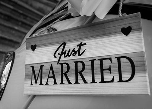 "A sign saying ""Just Married"" hangs on the outside of a car"