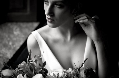 Bride gazes out the window in her wedding dress while holding a flower bouquet