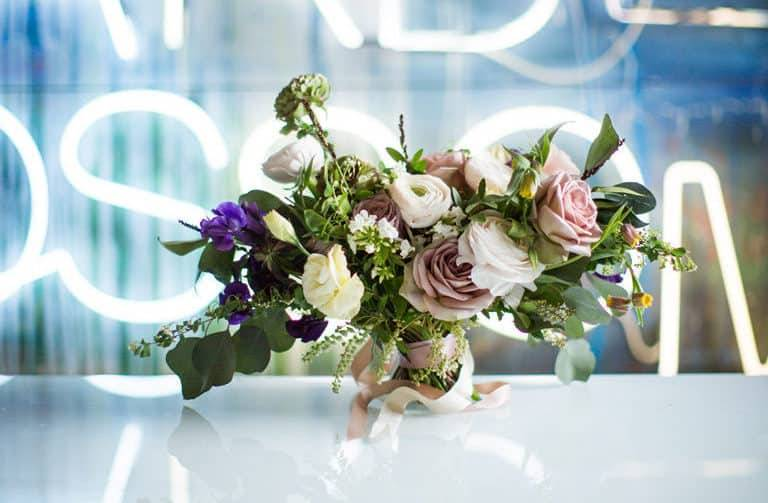 Intricate centrepiece flower arrangement on glass table with artwork behind