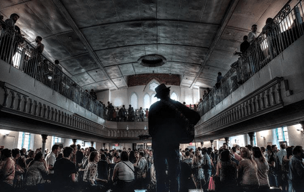 rear shot of performer at the Berkeley Church with a large audience watching
