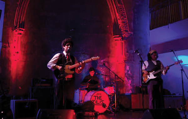 Guitar player and drummer performing with red lighting lighting the walls of the Berkeley Church