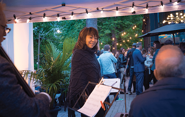 June Garber performs Jazz on the patio of the Bicycle Club Toronto with strong lights in the background
