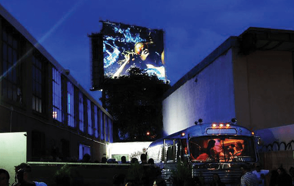 Night time at Airship37, a big screen is projecting an image.