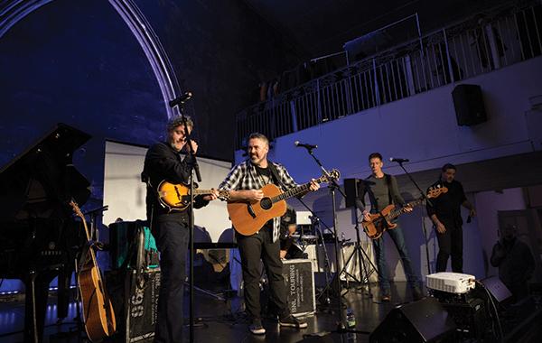 three band members at playing guitar and performing at the Berkeley Church