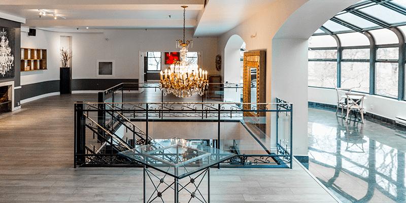 La Maquette empty venue featuring solarium, grand staircase and chandelier