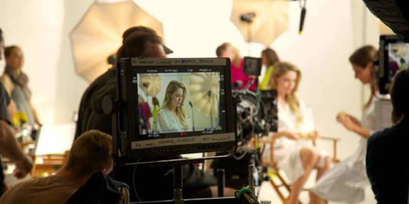 Monitor in forefront with model and umbrella light shades in the background while photoshoot is ocurring