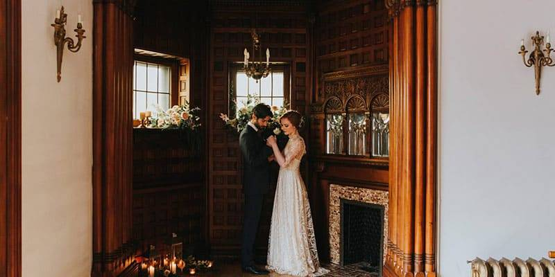 Bride and groom share holding a flower and eachother's hands while standing in the fireplace alcove at Berkeley Bicycle Club