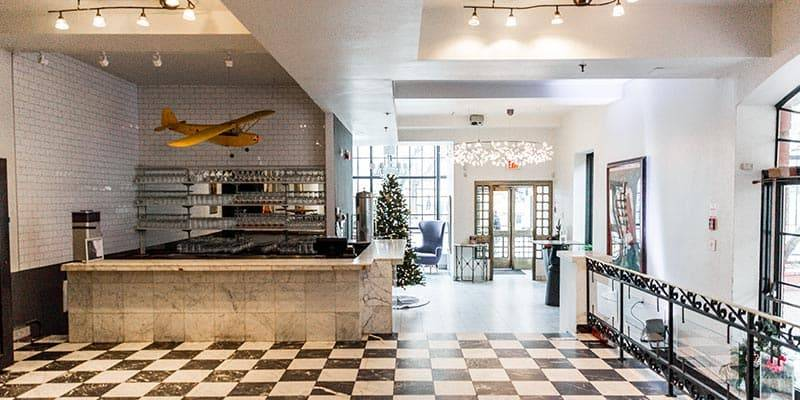Black and white checkered marble floors looking out onto king street with vintage yellow airplane hanging from ceiling