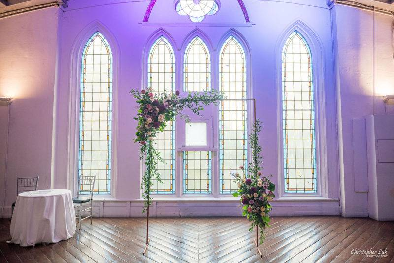 Cute simple wedding ceremony arch in front of stained glass window at berkeley church toronto