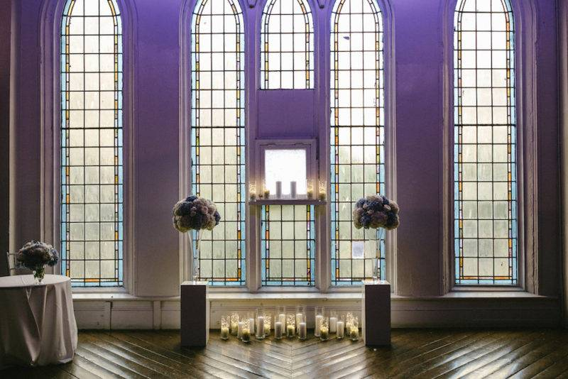 Stained glass windows and high floral arrangement Berkeley church Toronto wedding ceremony